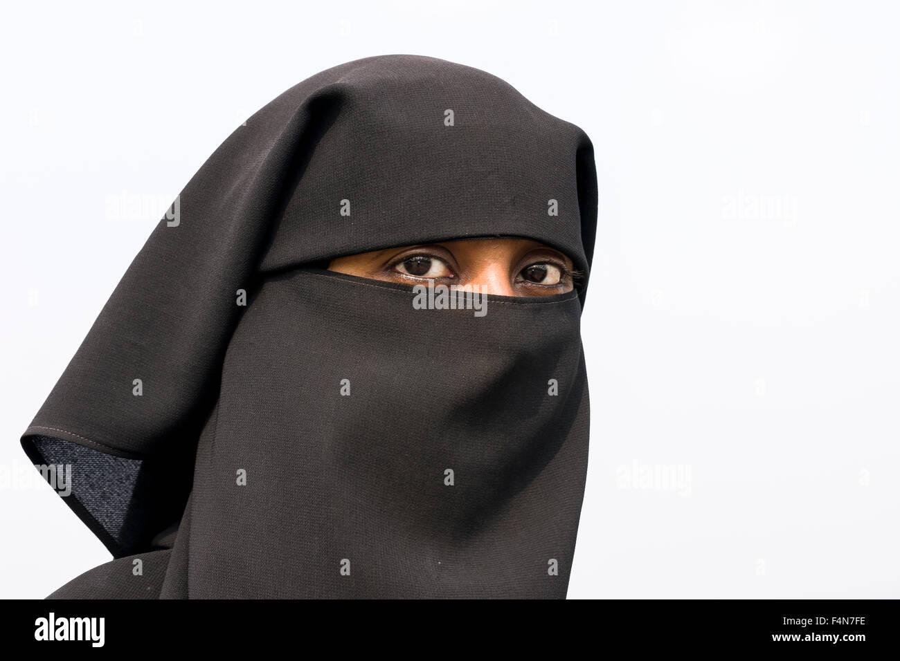 A portrait of a muslim woman dressed in the traditional black burka including the hijab - Stock Image