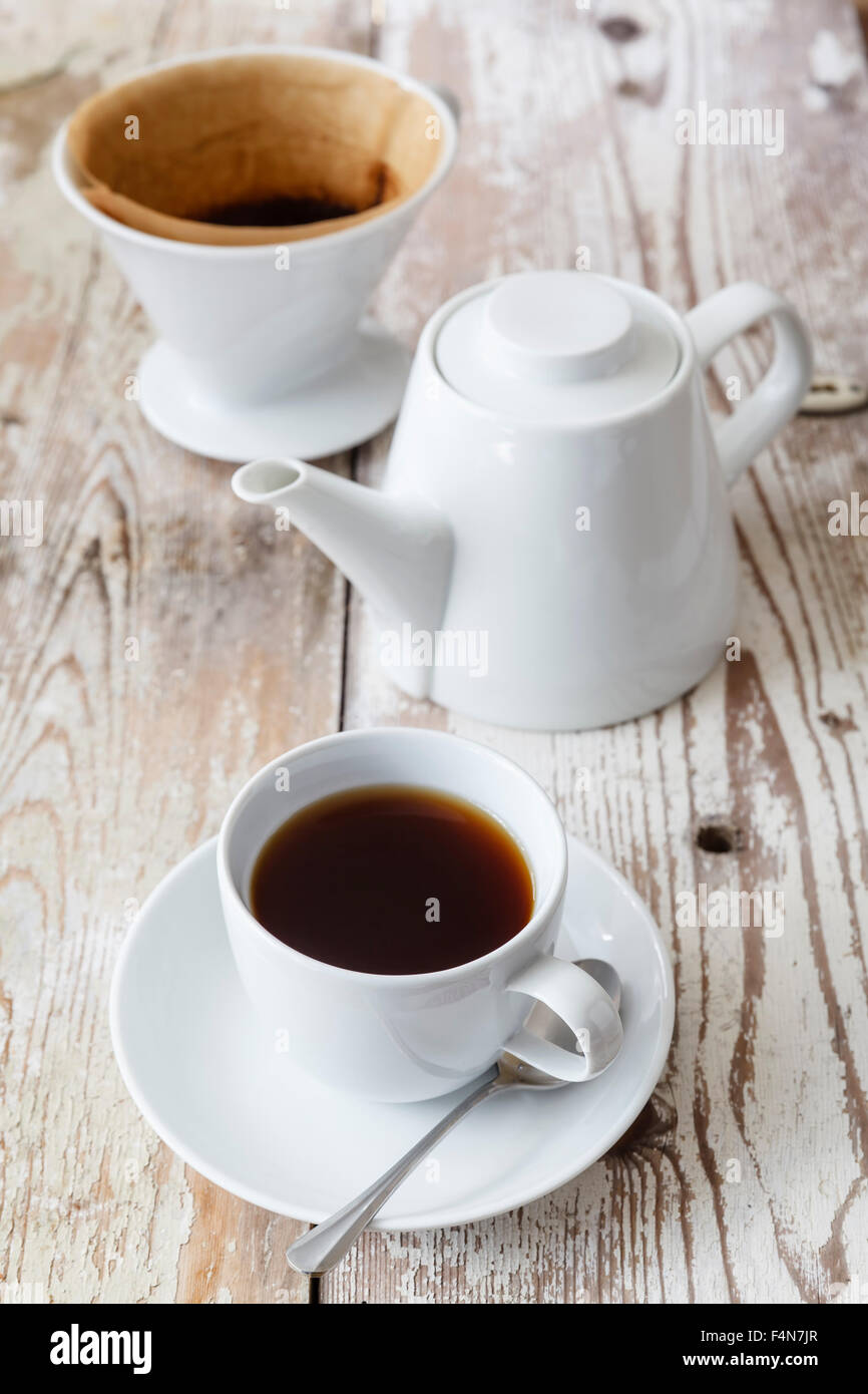 Cup of black filtered coffee and coffee pot on wood - Stock Image