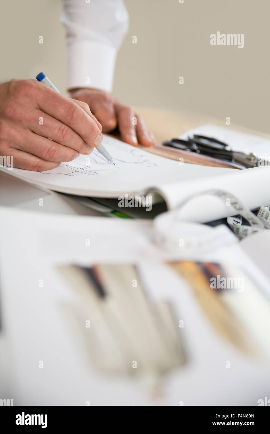 Tailor drawing cut pattern - Stock Image