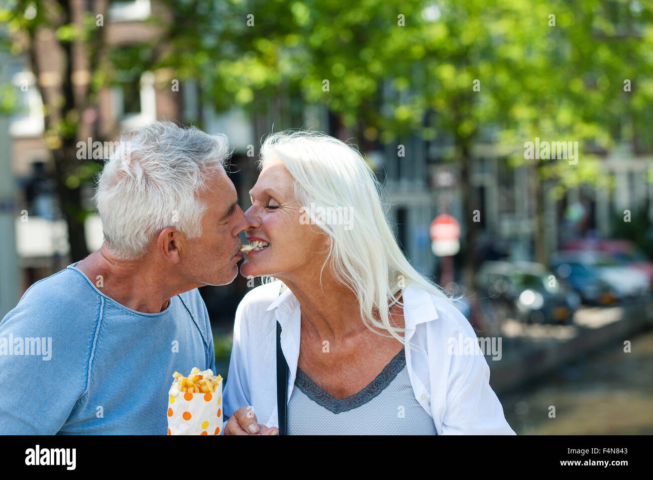 Netherlands, Amsterdam, happy senior couple sharing French Fries - Stock Image