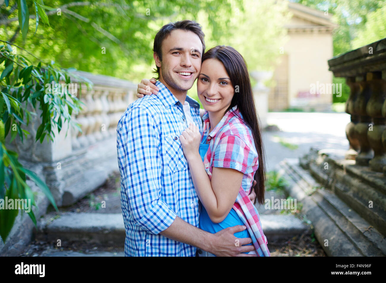 Young couple in embrace looking at camera outdoors - Stock Image