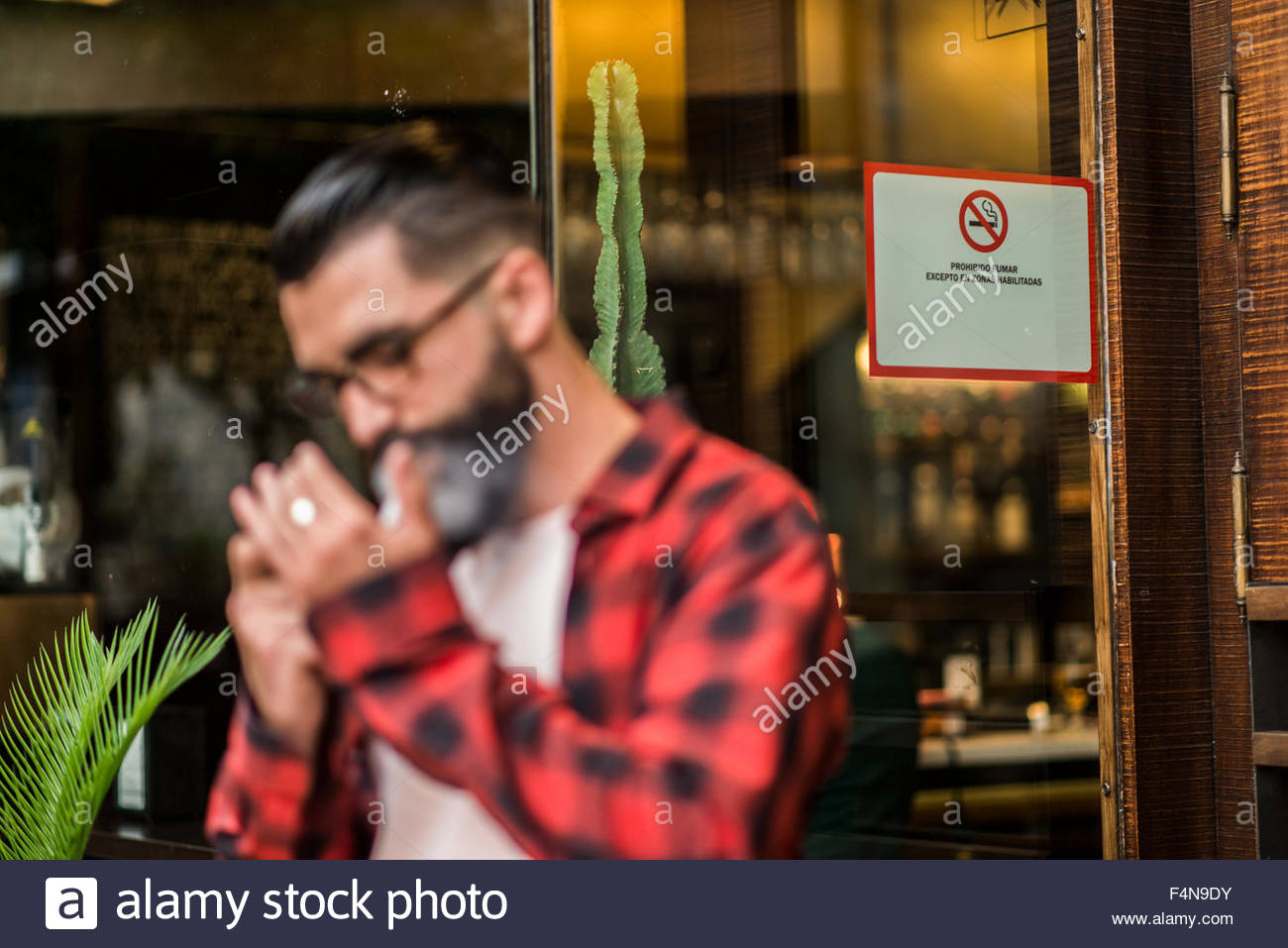 Hipster lighting a cigarette in front of a bar with smoking ban - Stock Image