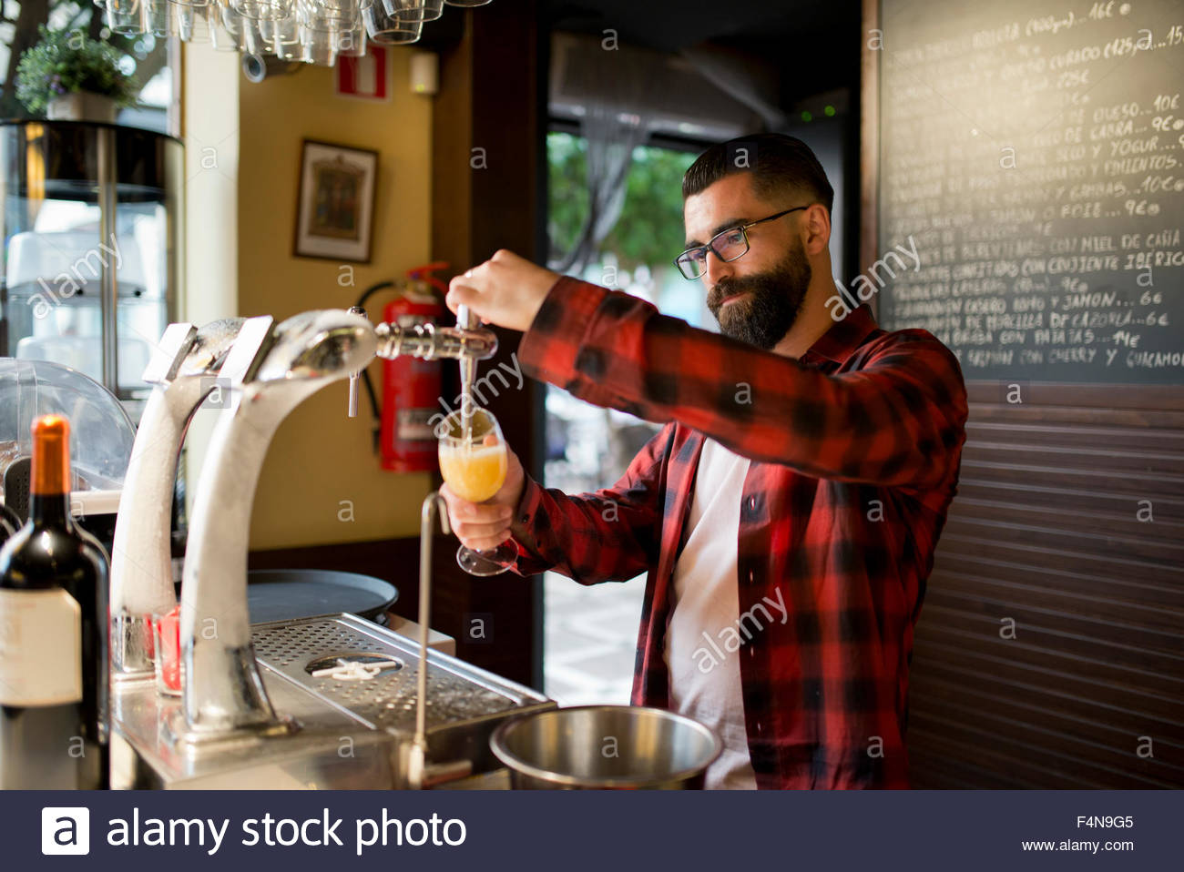 Man tapping beer in a pub - Stock Image