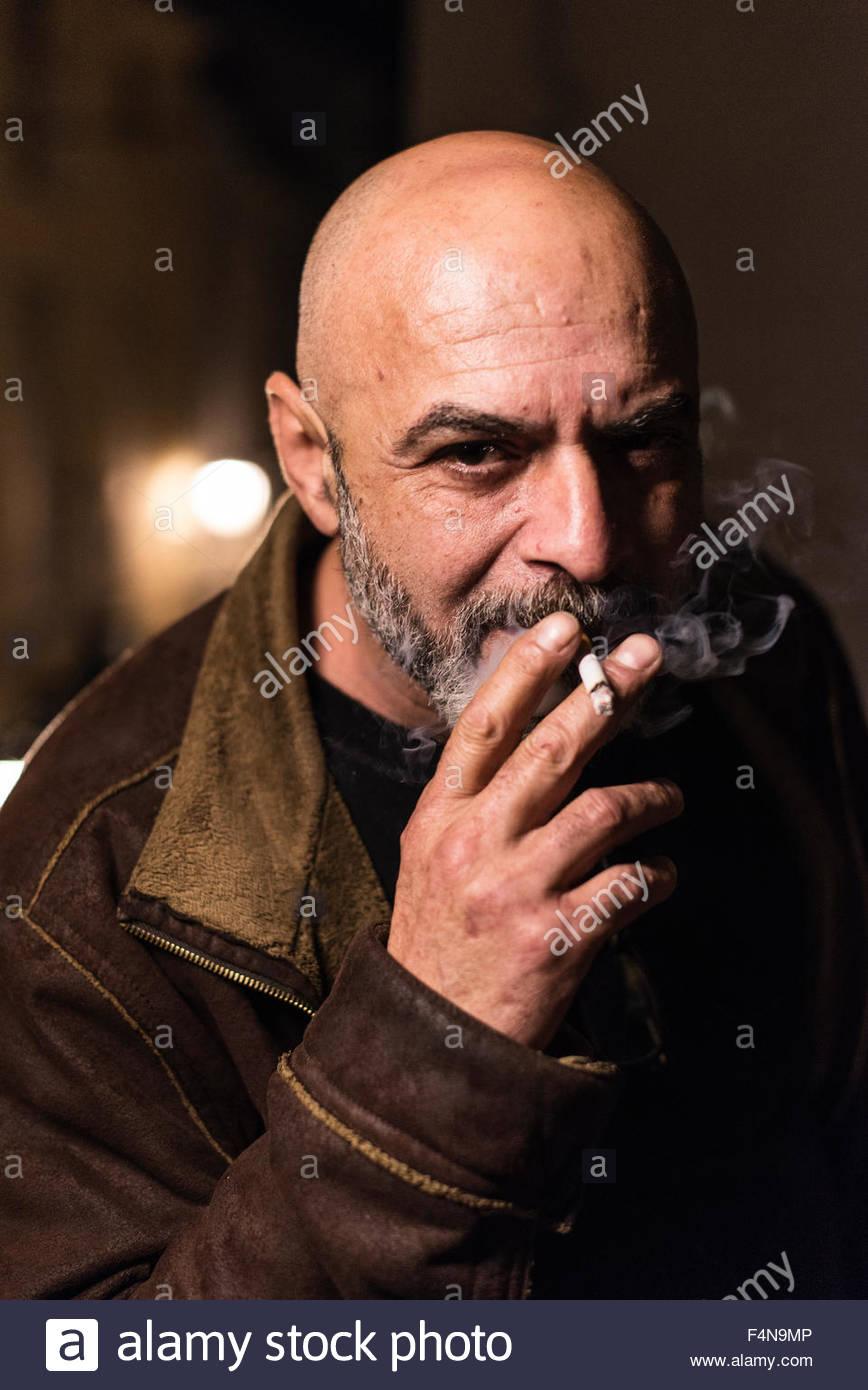 Portrait of smoking bald man - Stock Image