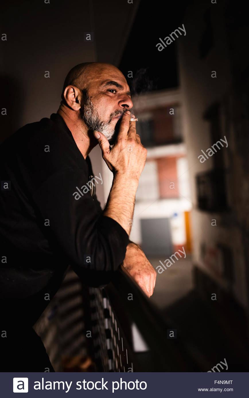 Bald man smoking on balcony at night - Stock Image