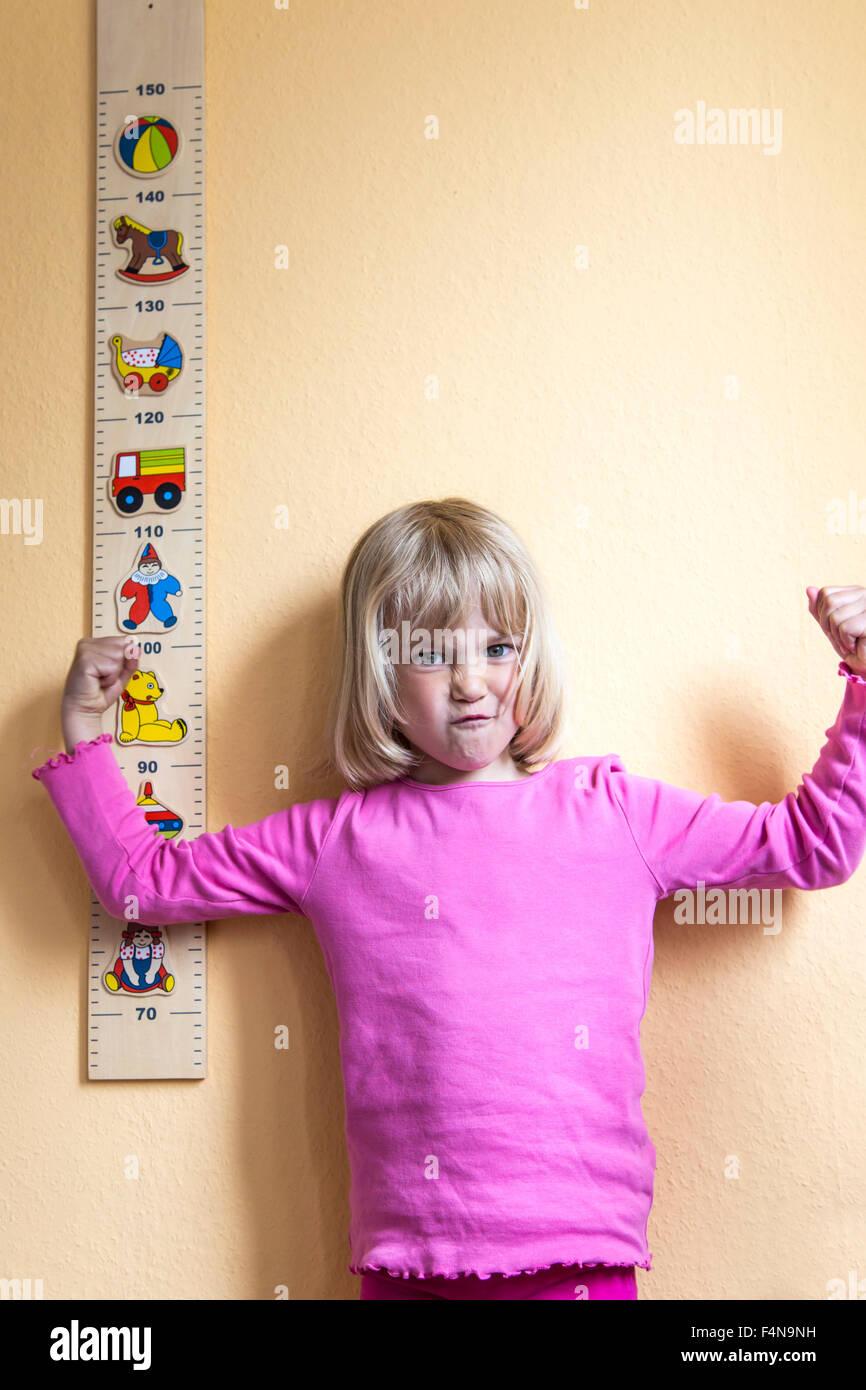 Portrait of grimacing little girl standing beside a yardstick - Stock Image