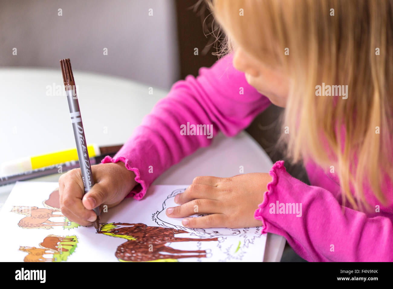 Little girl colouring horses in her colouring book Stock ...