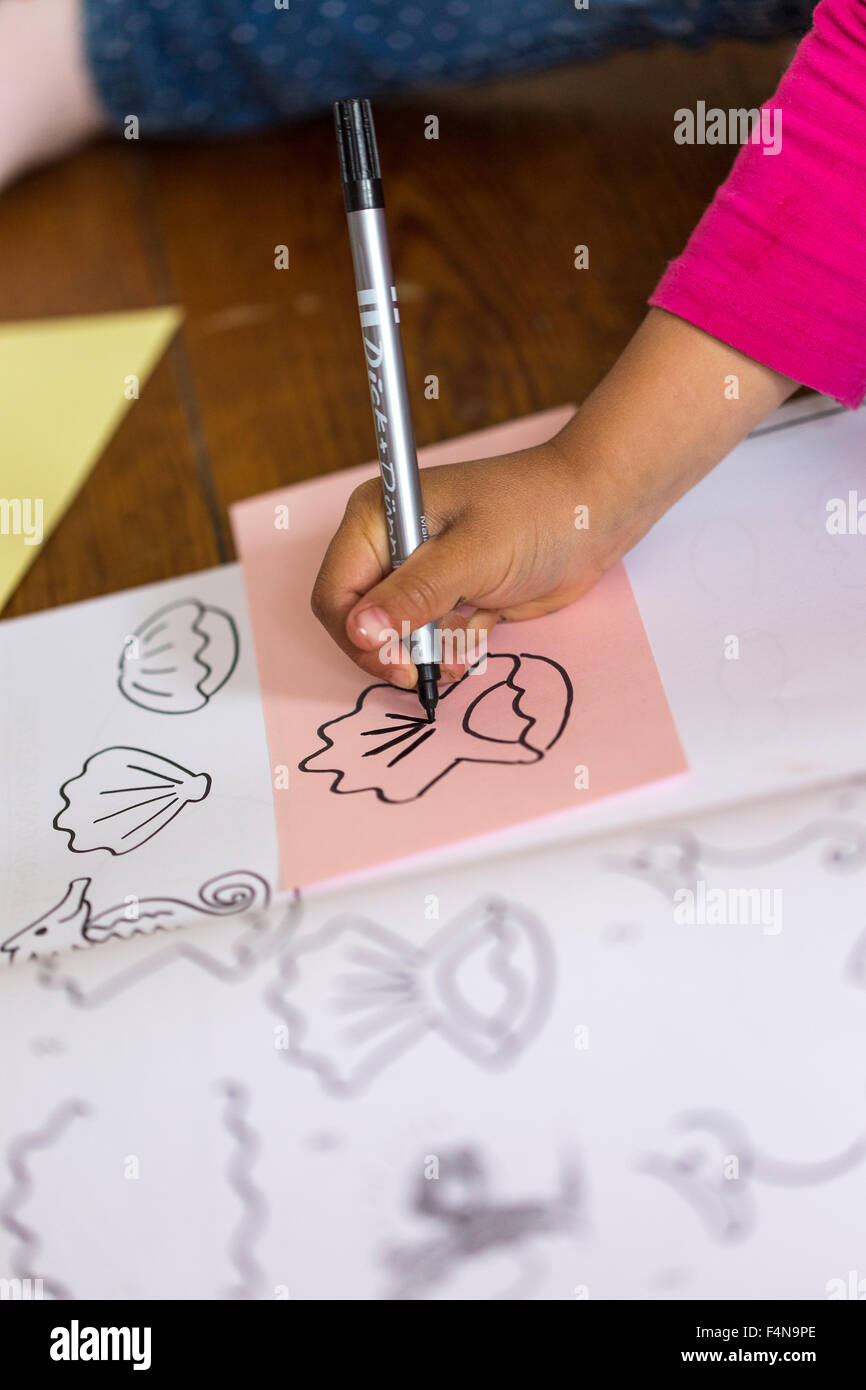 Hand of little girl drawing forms - Stock Image