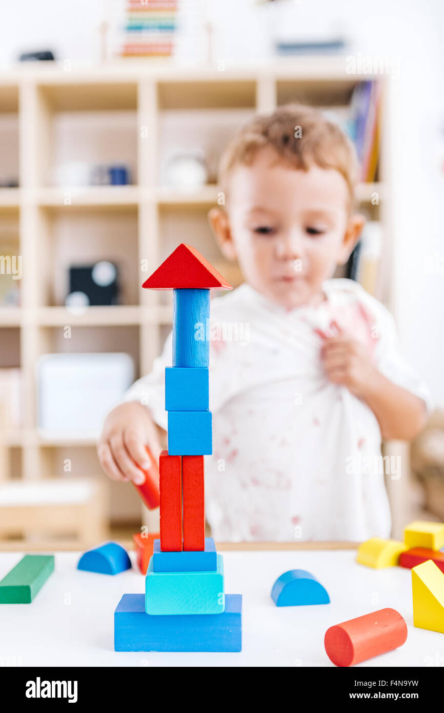 Little boy built a tower with blue and red building bricks - Stock Image
