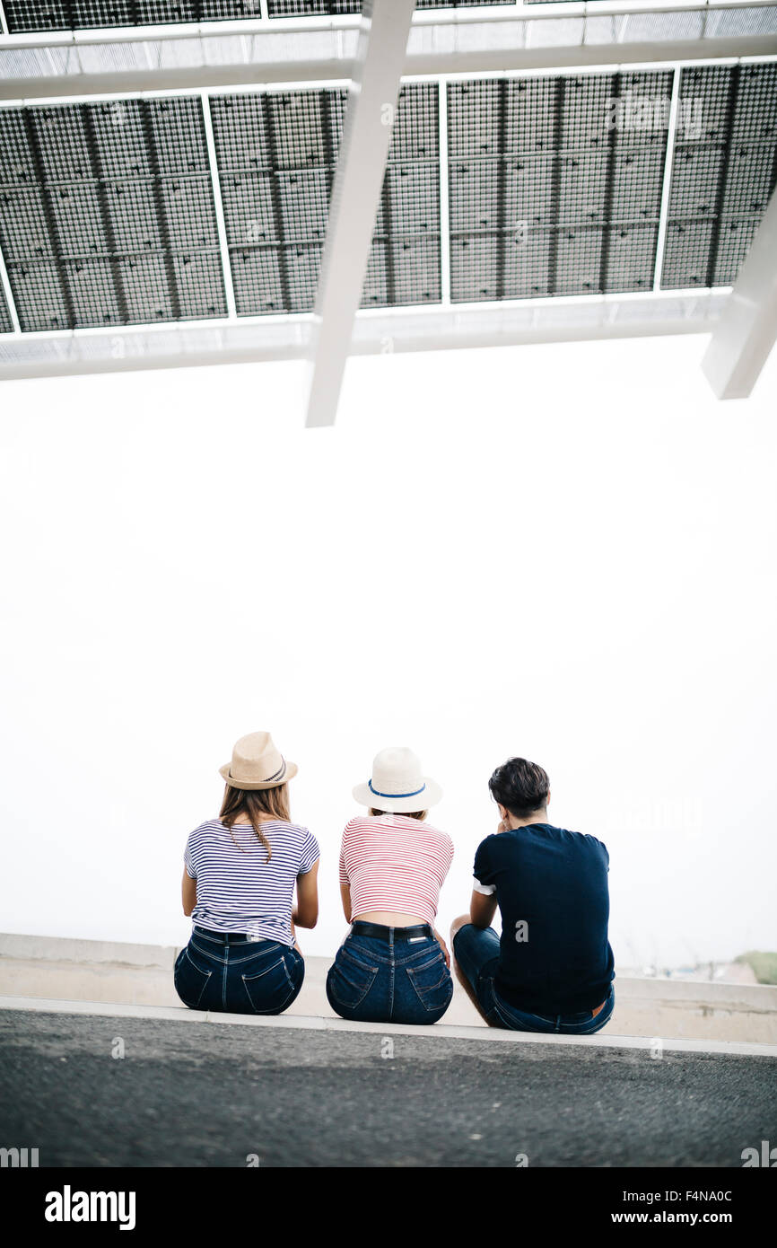 Back view of three friends sitting side by side on a step - Stock Image