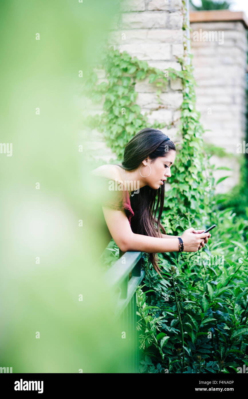 Young woman leaning on railing using cell phone Stock Photo