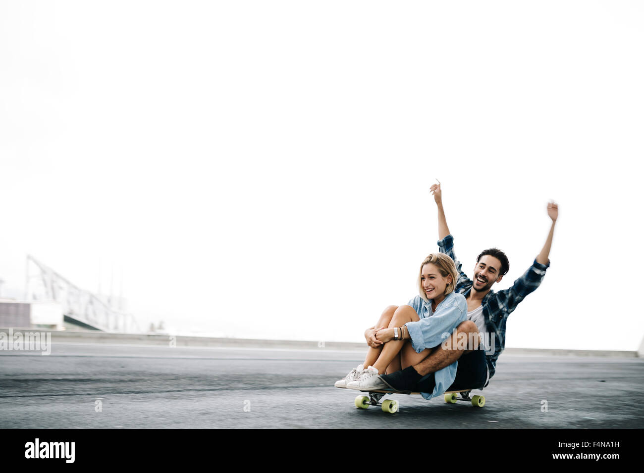 Young couple cruising on a longboard Stock Photo
