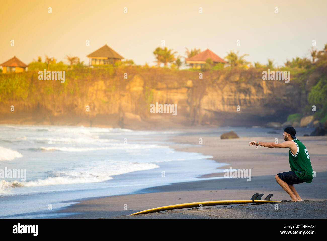 Indonesia, Bali, surfer on the beach doing a knee bend - Stock Image
