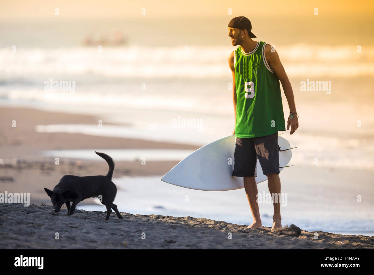 Indonesia, Bali, surfer and dog on the beach - Stock Image