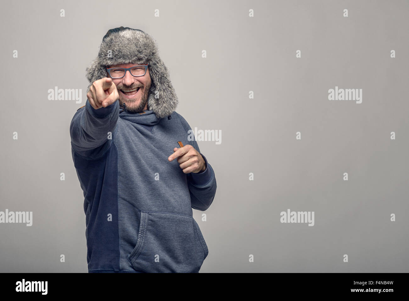 Laughing jovial man wearing glasses and a furry winter hat standing pointing at the camera with a playful expression, over grey Stock Photo