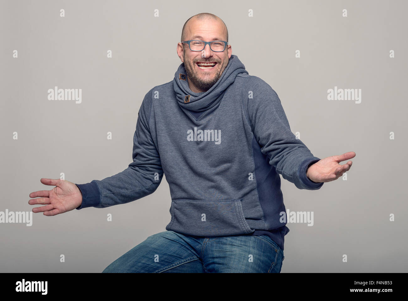 Charismatic balding middle-aged man wearing glasses laughing and shrugging his shoulders to show his ignorance, - Stock Image