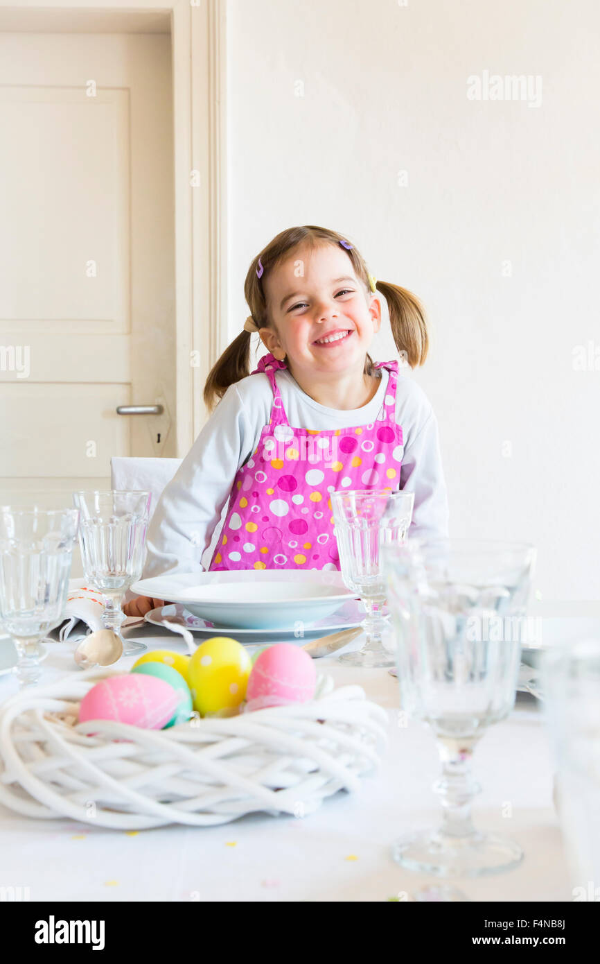 Portrait of smiling little girl sitting at laid table - Stock Image