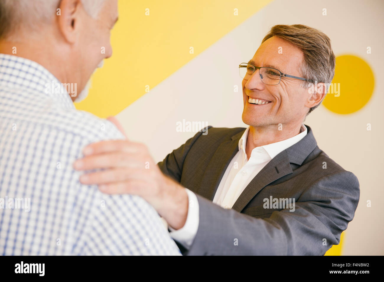Portrait of smiling mature man talking to another man in an office - Stock Image
