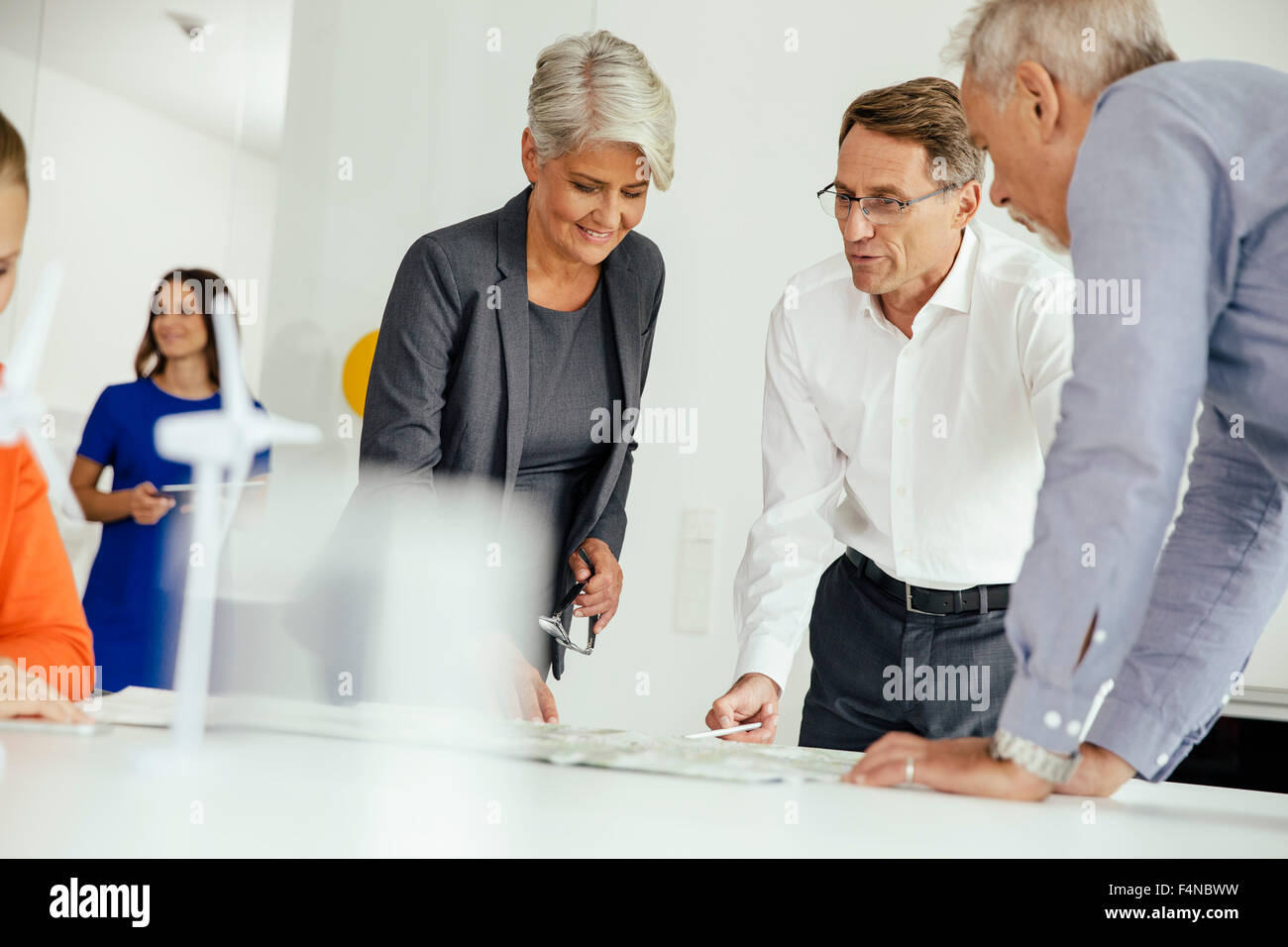 Business people discussing plan with wind turbine model on conference table - Stock Image