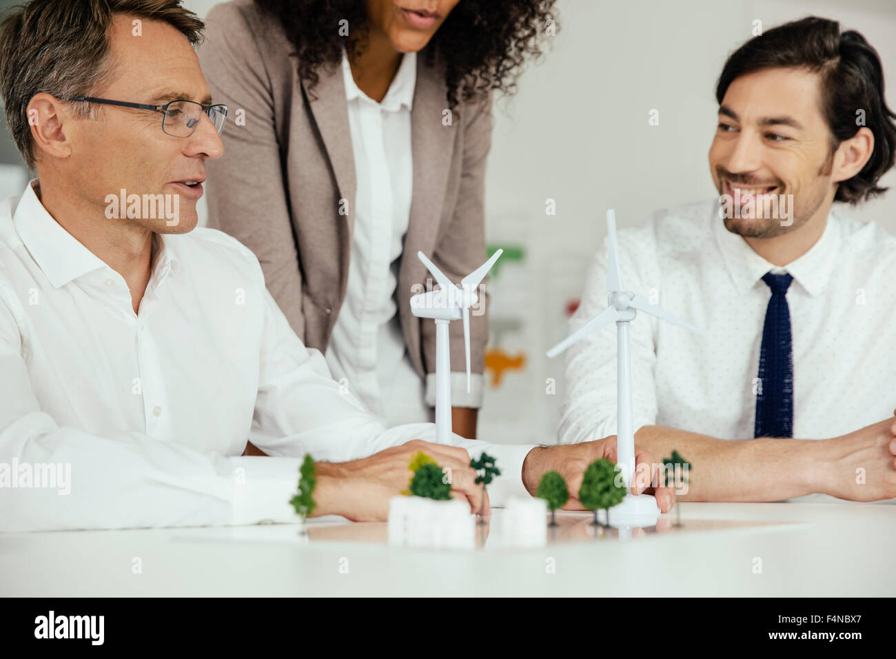 Business people discussing wind turbine model and houses on conference table - Stock Image
