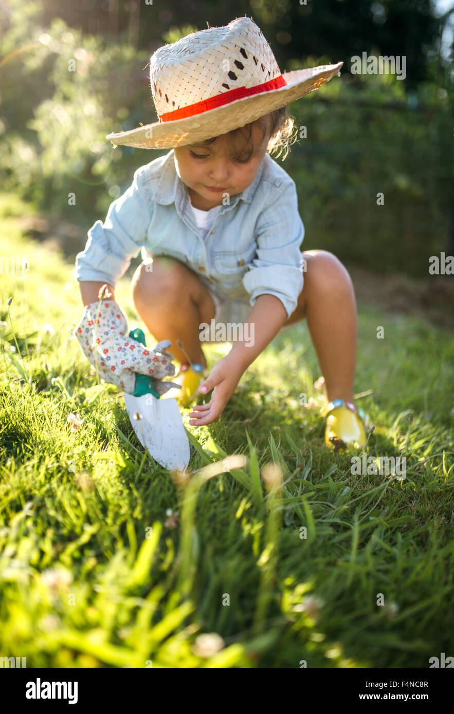 Little girl crouching with gardening glove and hand trowel on a meadow - Stock Image
