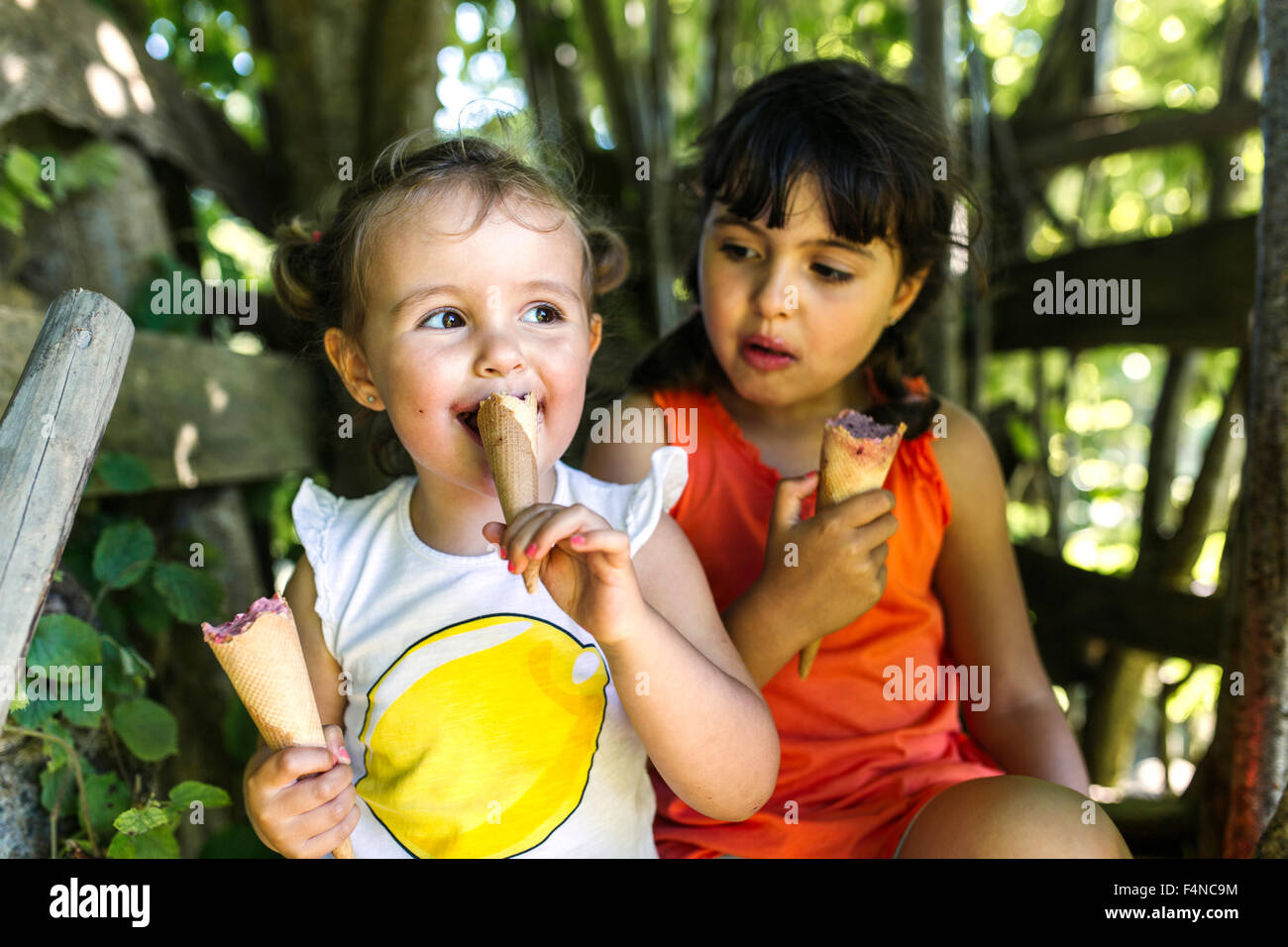 Two little sisters eating ice cream - Stock Image
