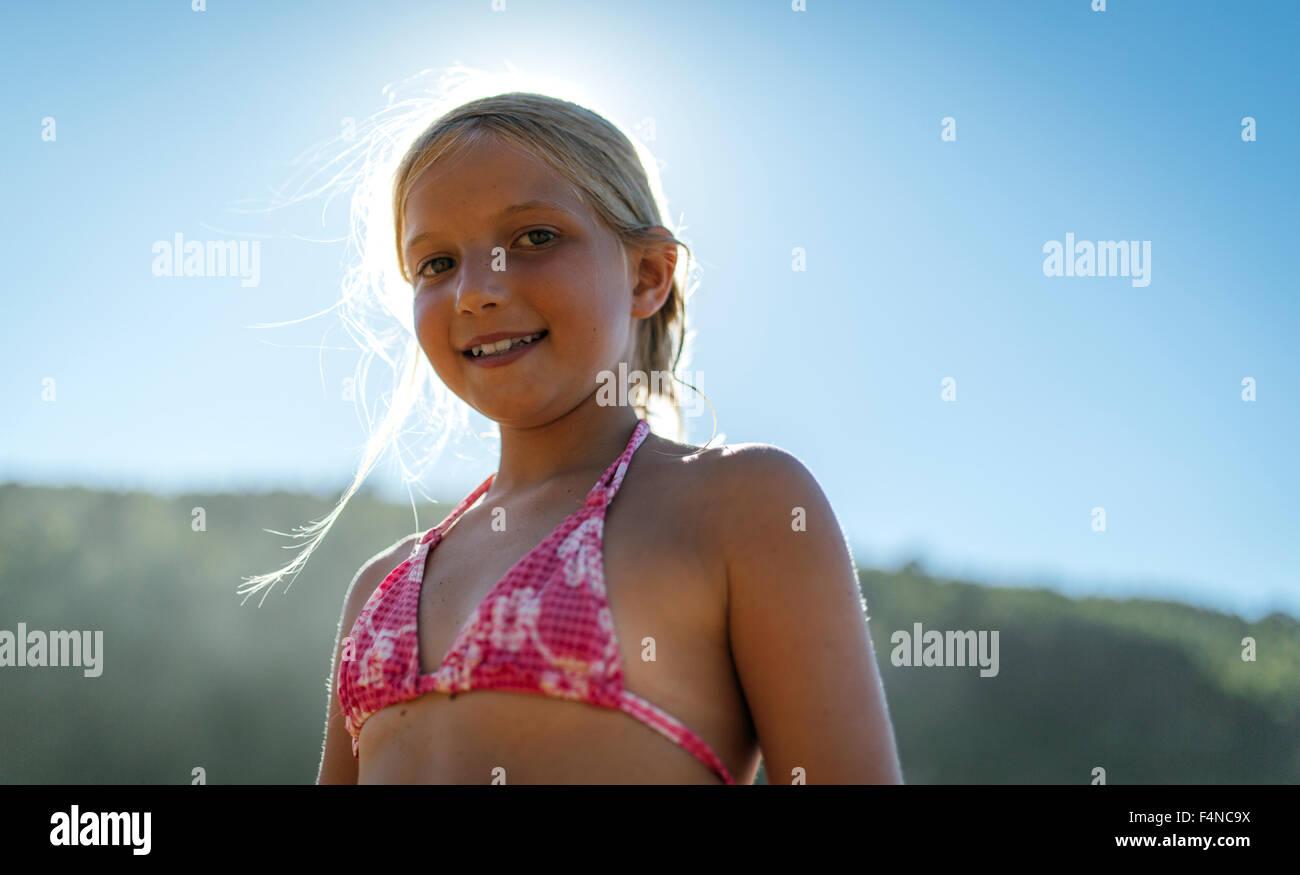 Portrait of a blond little girl wearing bikini top - Stock Image