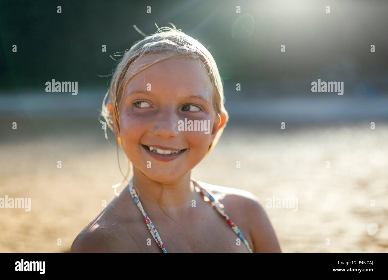 Portrait of blond girl with wet hair on the beach - Stock Image