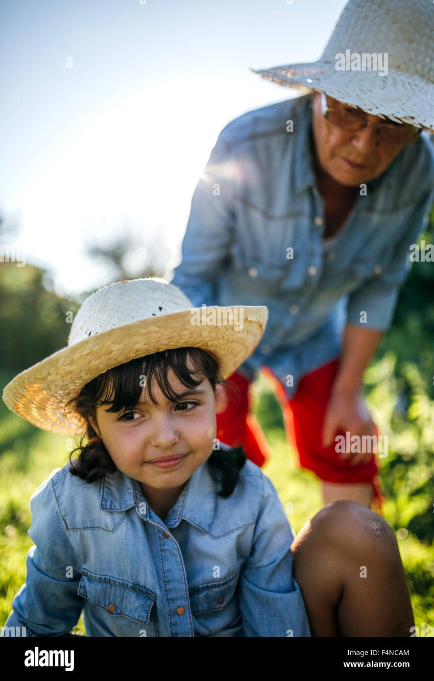 Senior woman and her  granddaughter in the garden - Stock Image