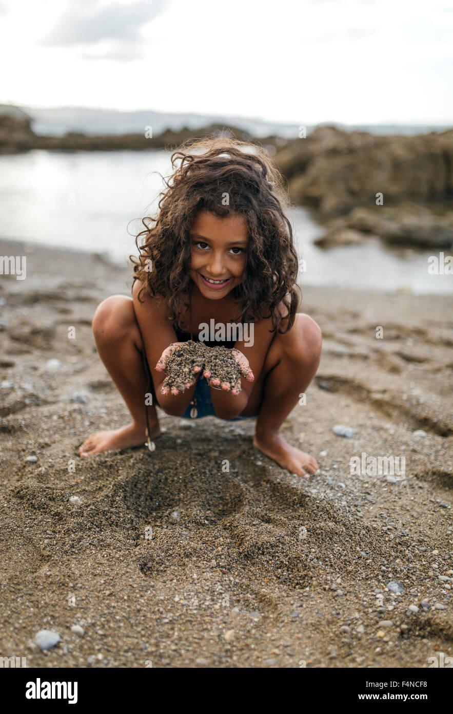 Spain Gijon Portrait Of Smiling Little Girl Holding Sand