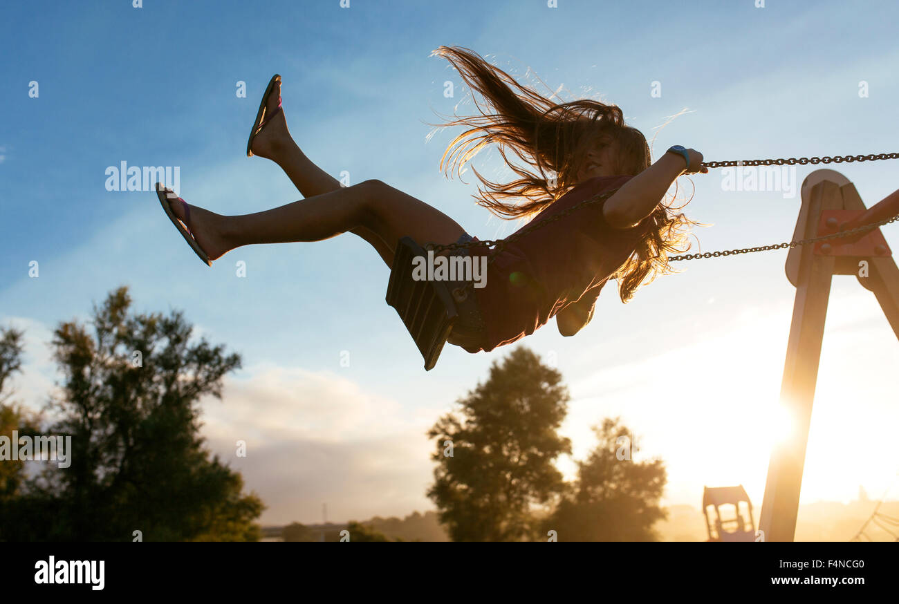 Girl with blowing hair on a swing at backlight Stock Photo