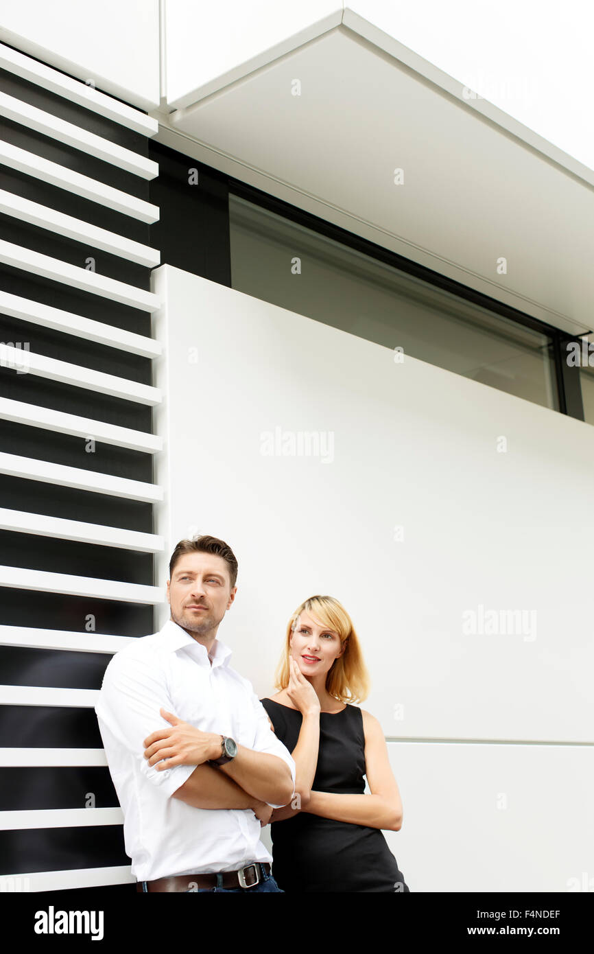Couple leaning against facade watching something - Stock Image