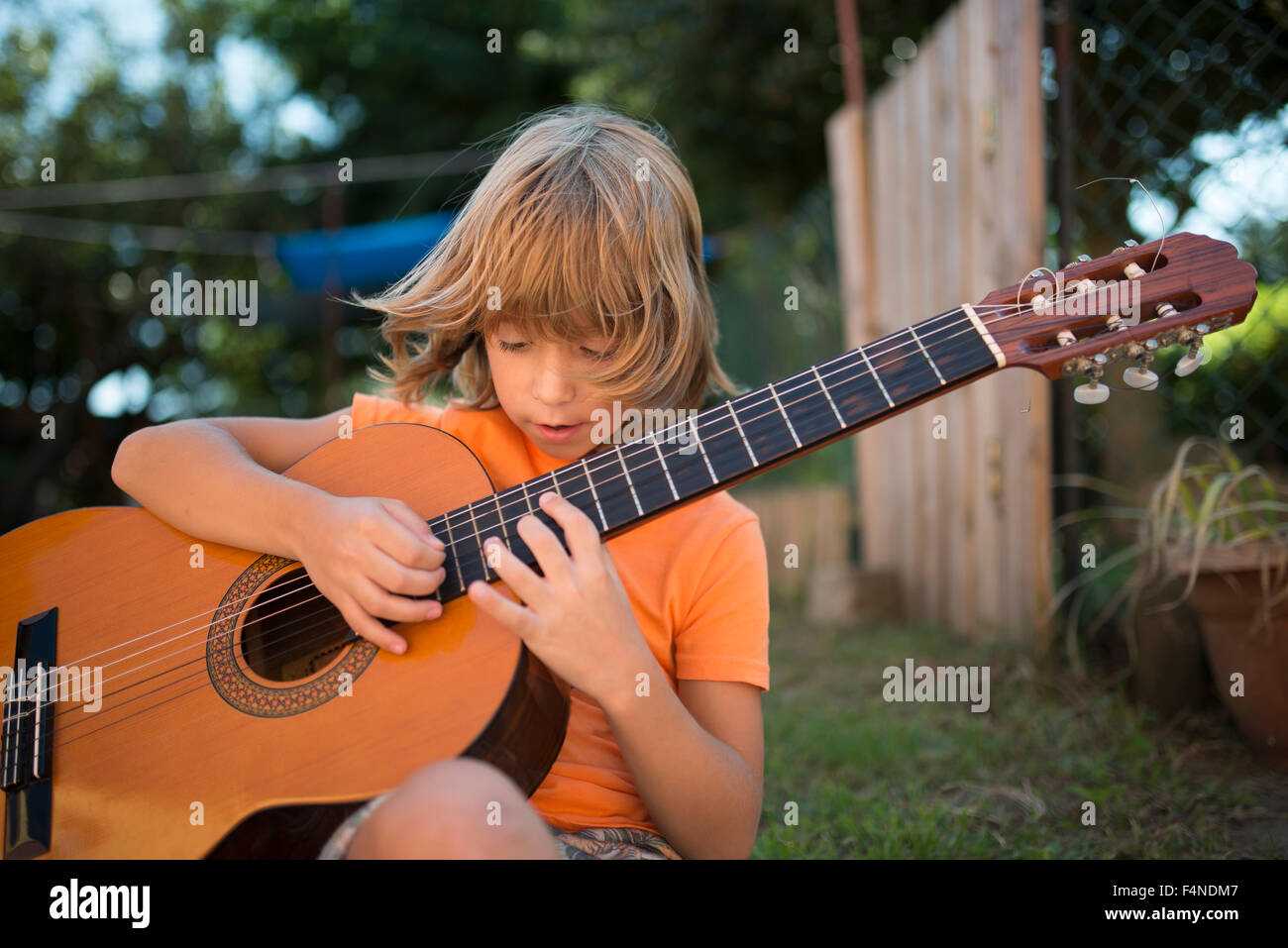 Spain, Long-haired blond boy playing spanish guitar outdoors - Stock Image