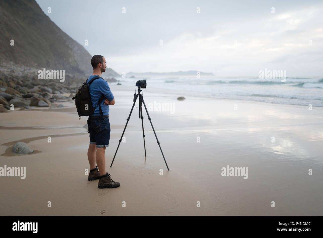Spain, Valdovino, photographer standing on the beach taking photos with a tripod Stock Photo