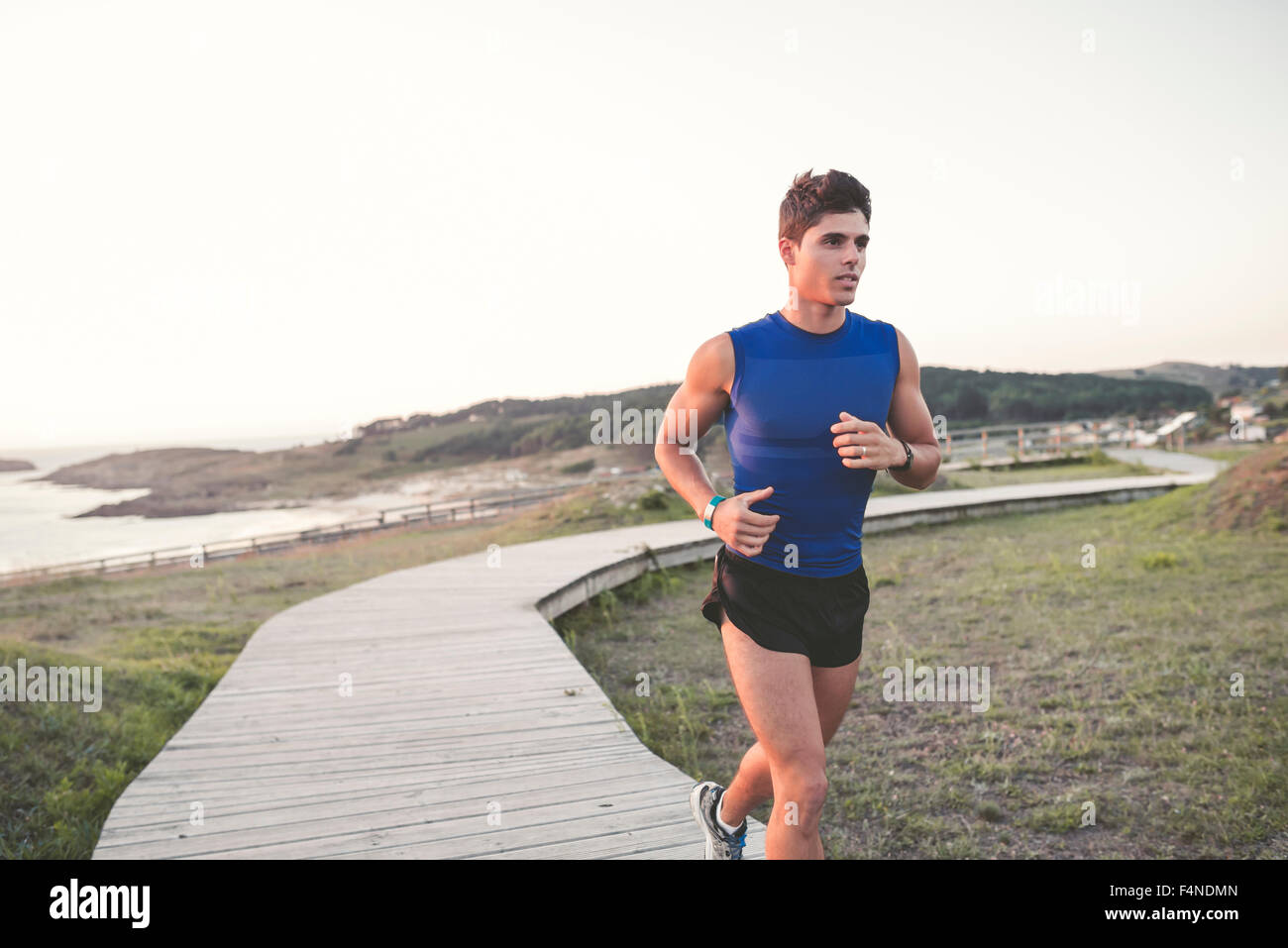 Spain, Ferrol, jogger running on a boardwalk - Stock Image