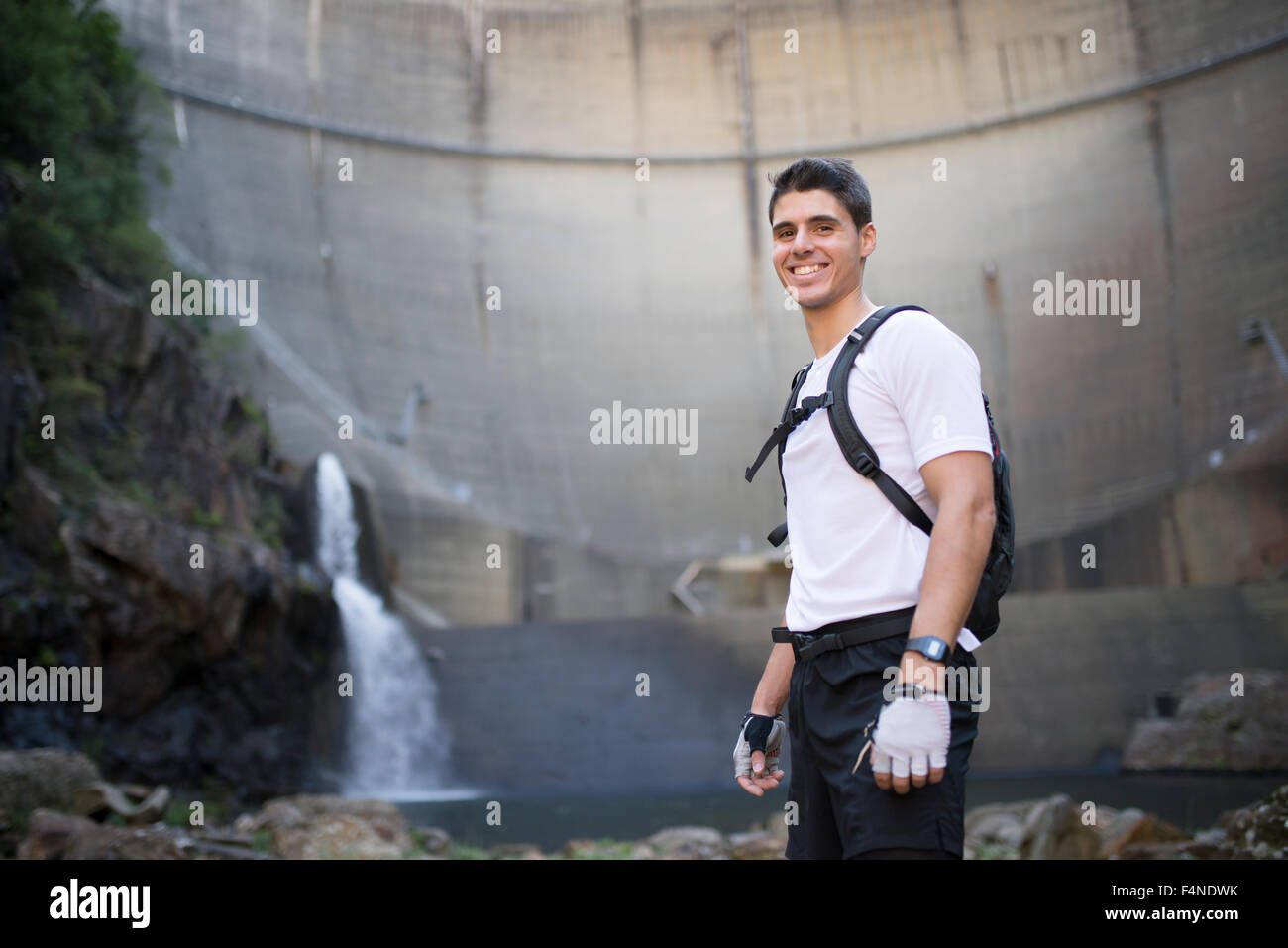 Smiling ultra trail runner with a dam in the background - Stock Image
