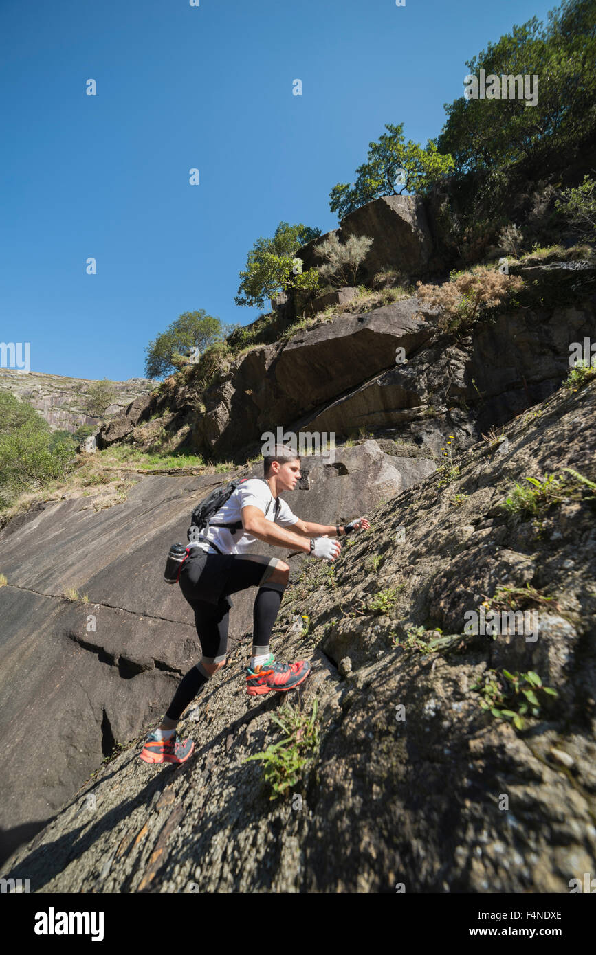 Spain, Galicia, A Capela, Ultra trail runner ascending a slope of rock - Stock Image