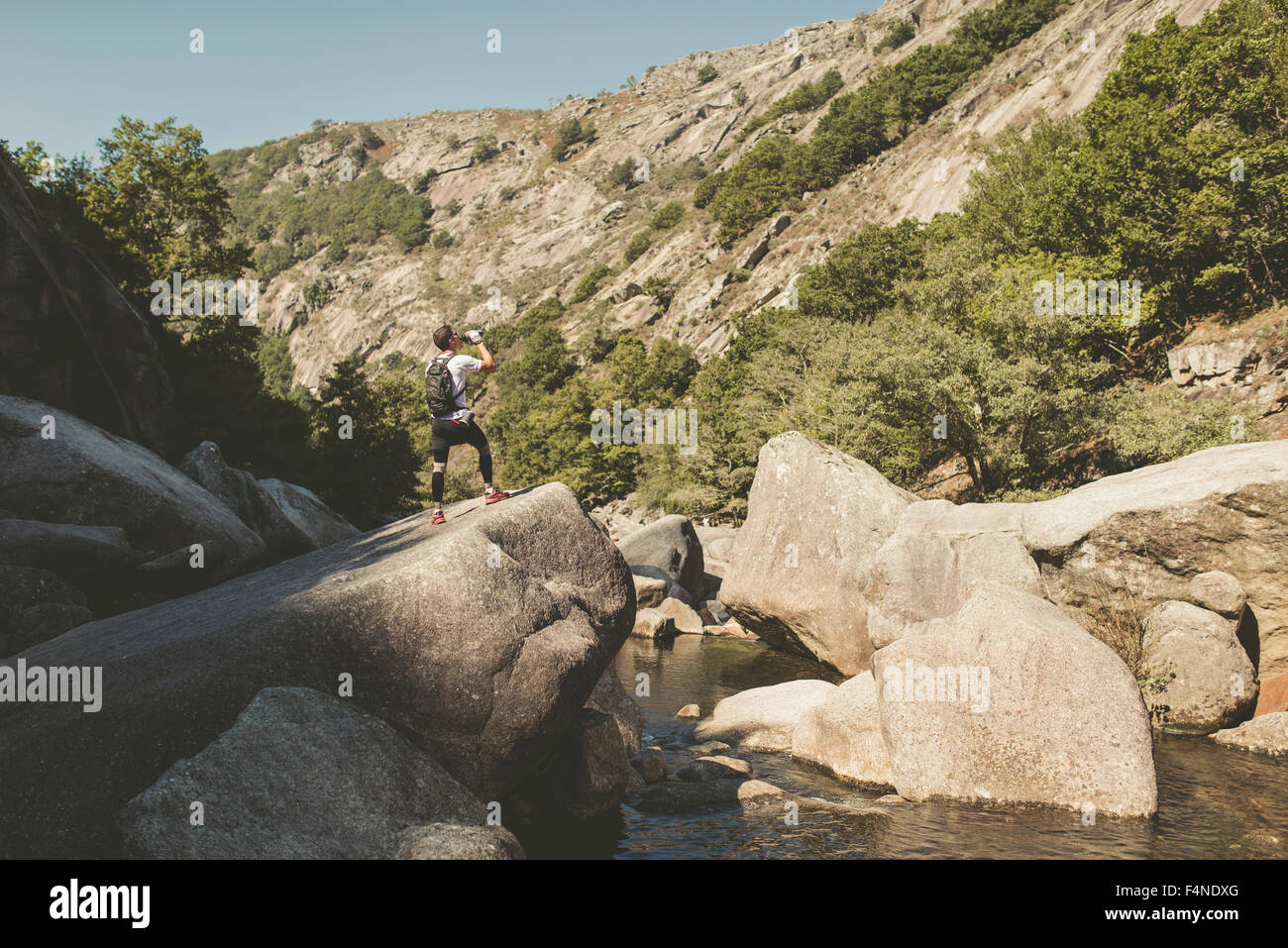 Spain, Galicia, A Capela, Ultra trail runner drinking at the canyon of Eume river - Stock Image