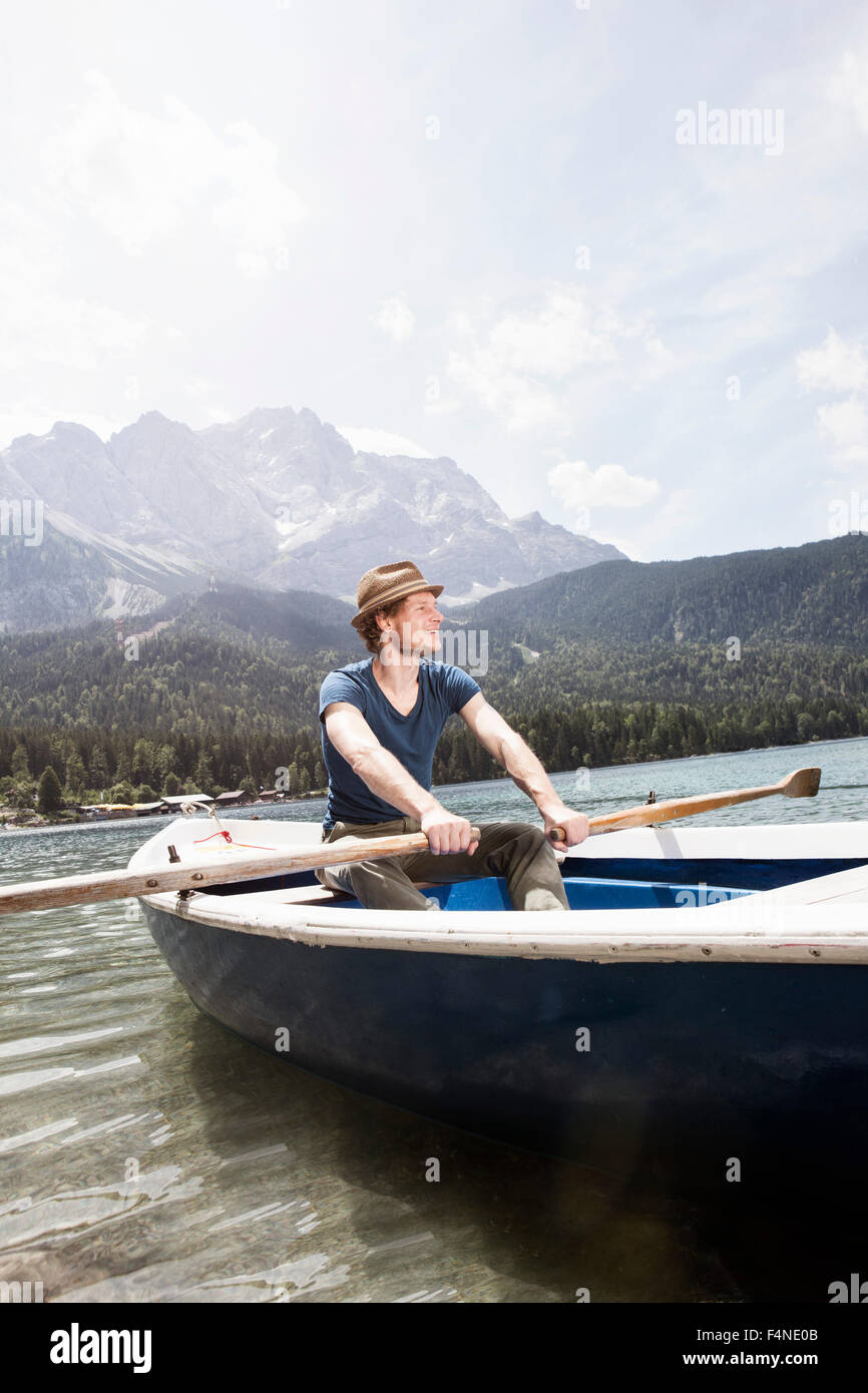 Germany, Bavaria, Eibsee, man in rowing boat on the lake - Stock Image