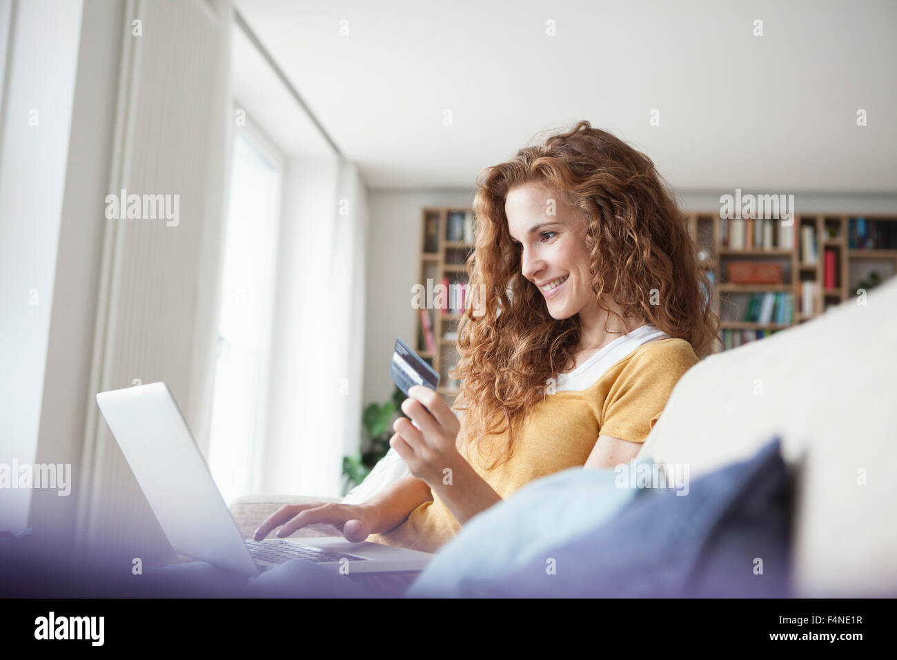 Smiling woman at home shopping online - Stock Image