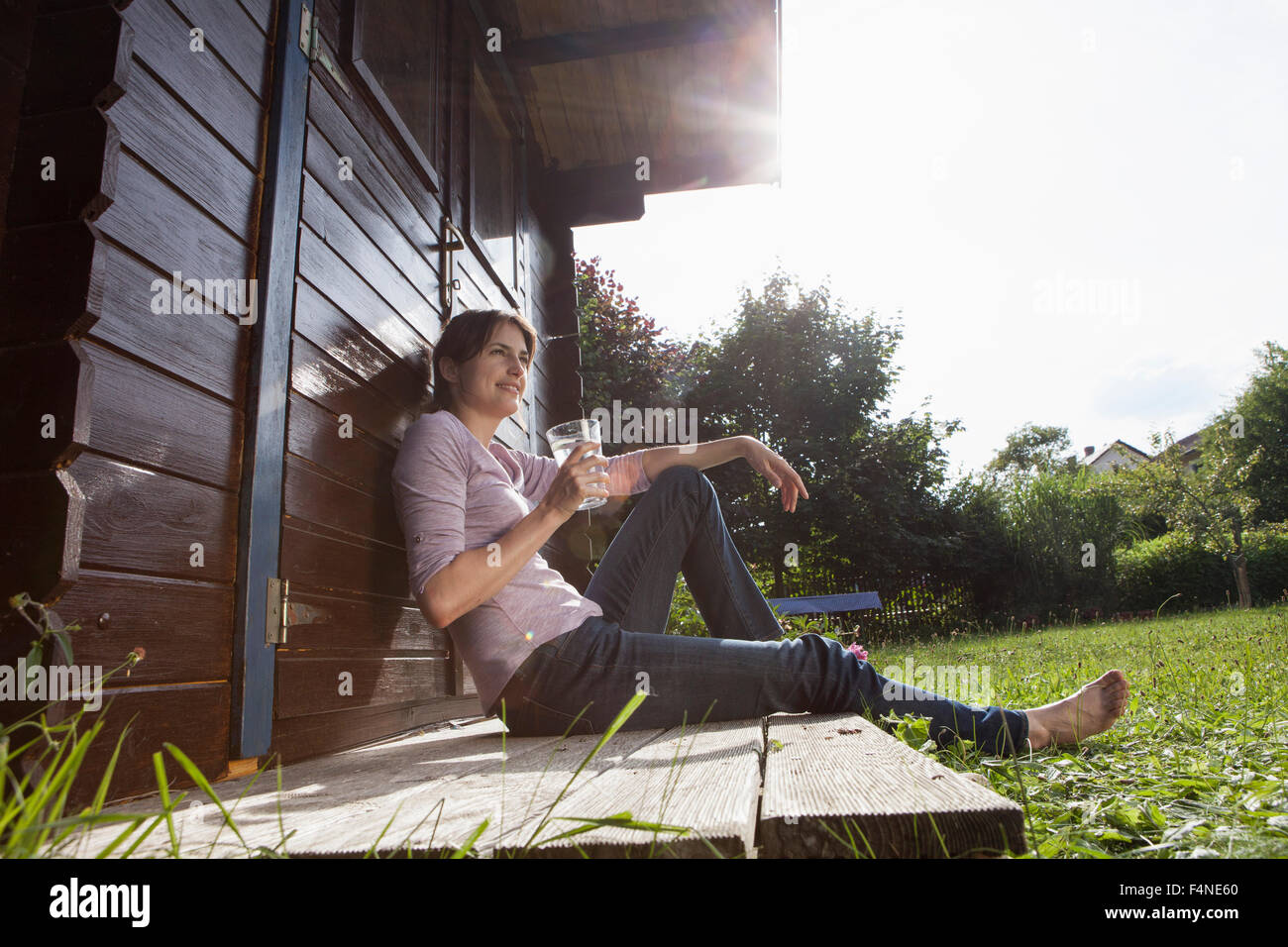 Smiling woman sitting at garden shed with glass of water - Stock Image