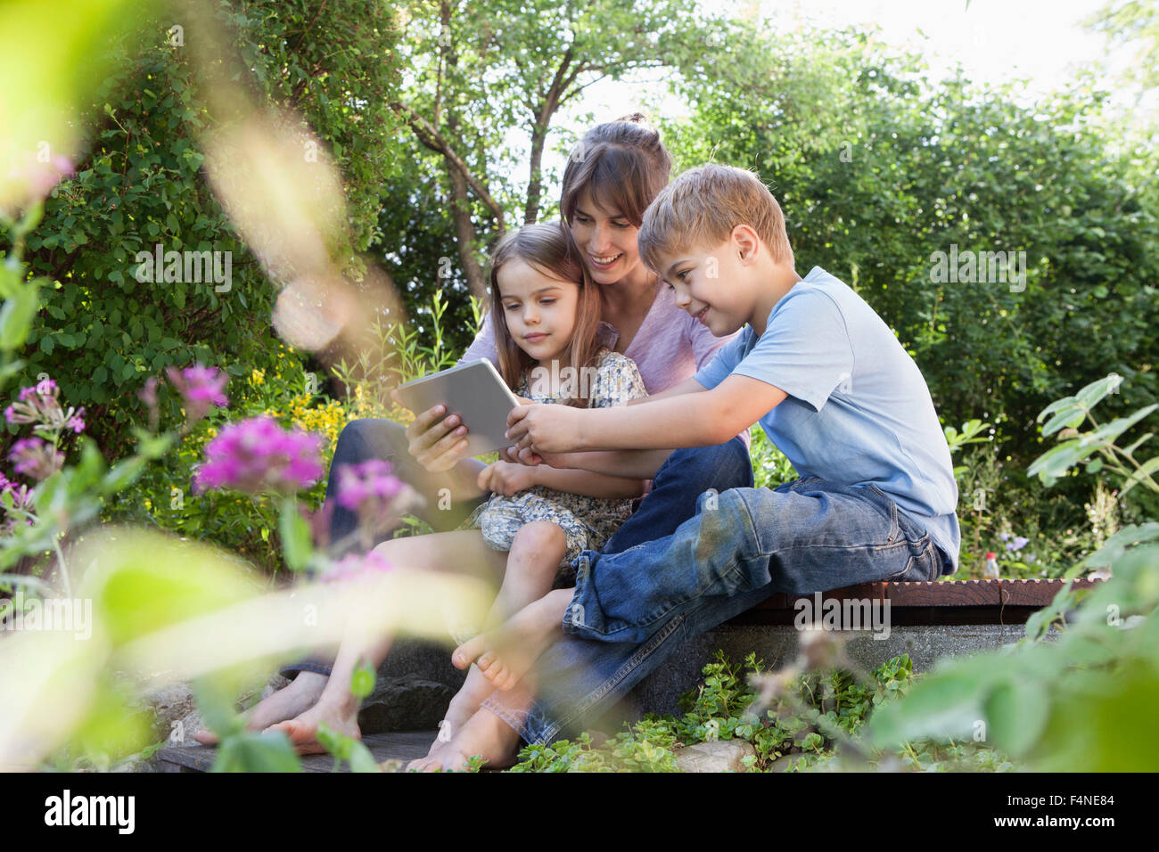 Mother, son and daughter with digital tablet in garden - Stock Image