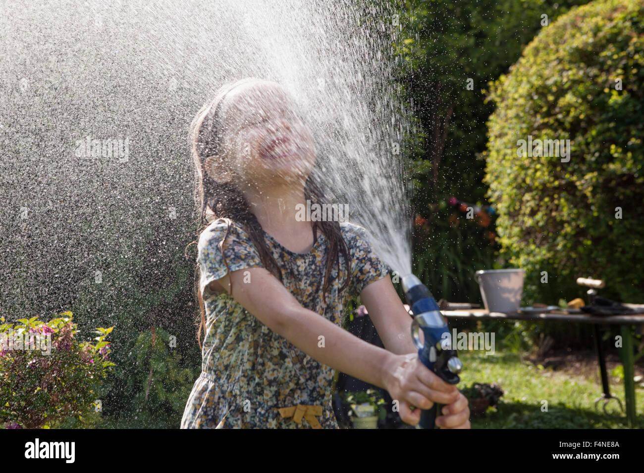 Girl splashing with water in garden - Stock Image