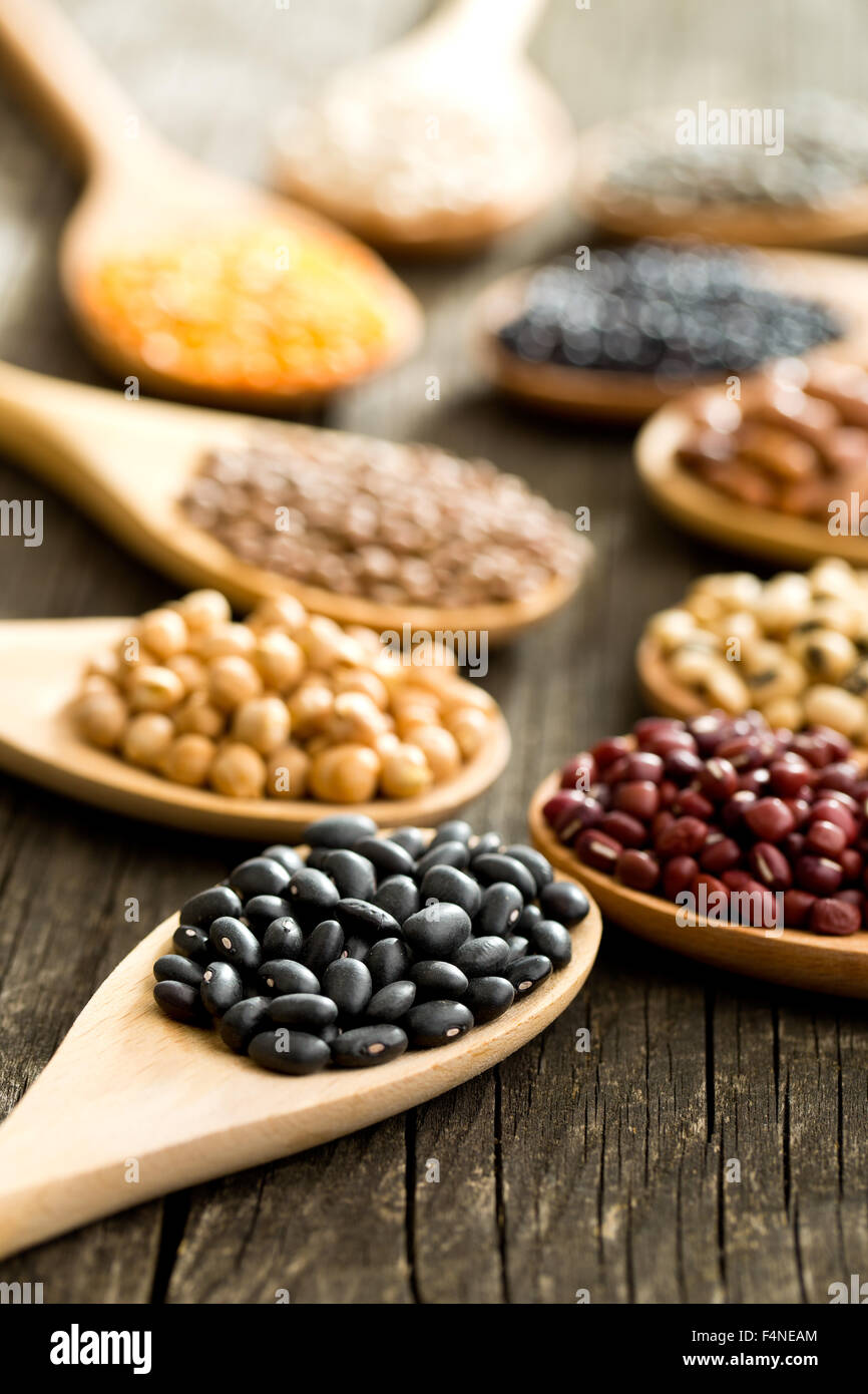 various dried legumes in wooden spoons on old table Stock Photo