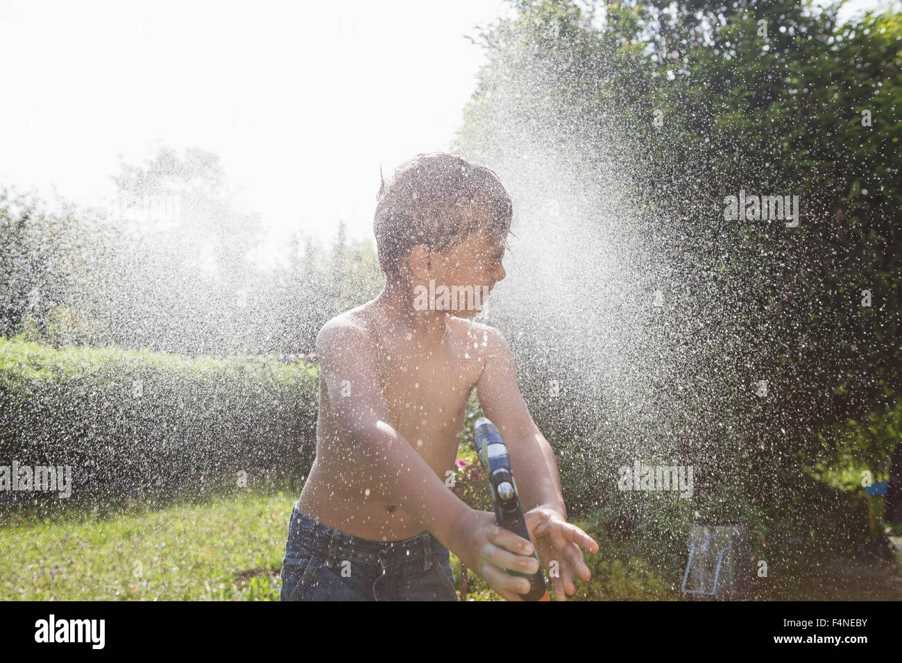 Boy splashing with water in garden - Stock Image