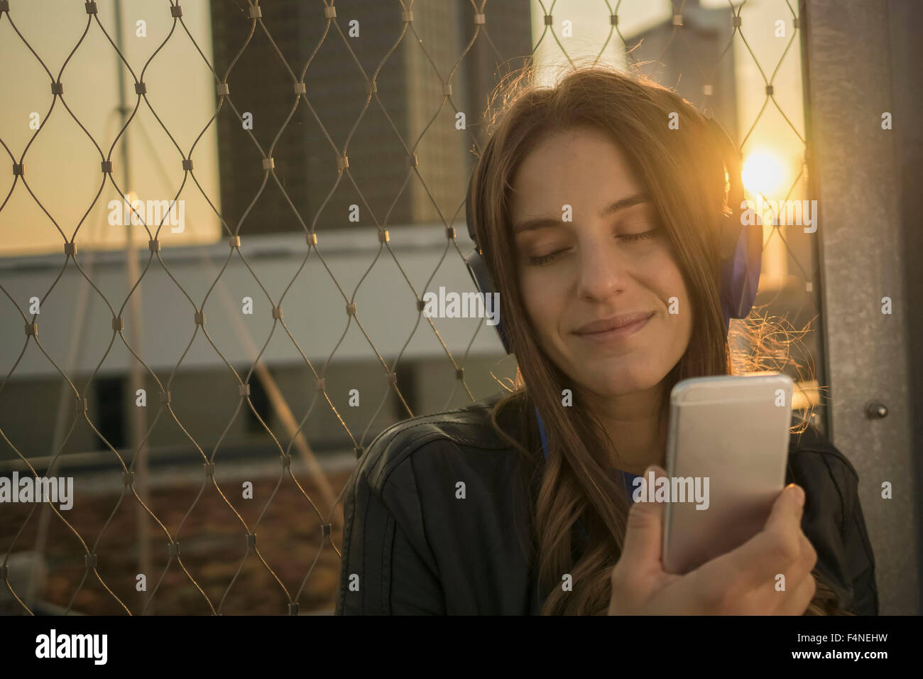 Portrait of smiling young woman with closed eyes hearing music with headphones at backlight - Stock Image