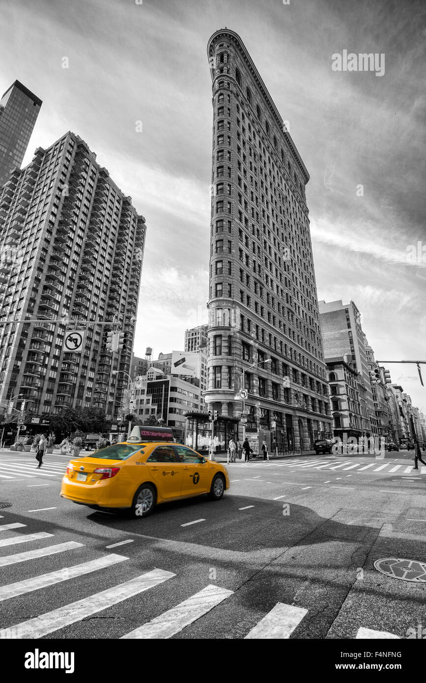 Selective colour image of the iconic Flatiron Building with a yellow cab, Manhattan New York USA - Stock Image