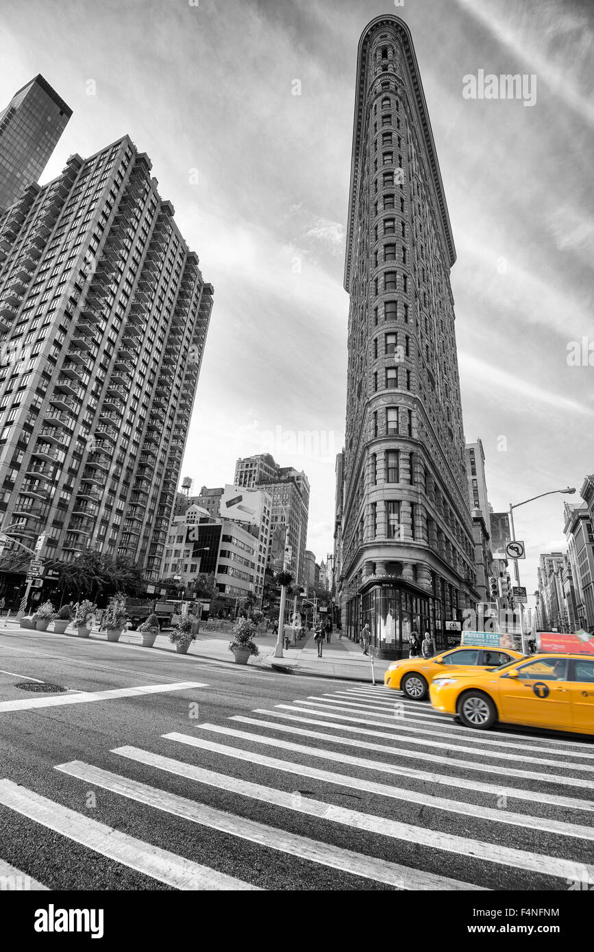 Selective colour image of the iconic Flatiron Building with two yellow cabs, Manhattan New York USA - Stock Image