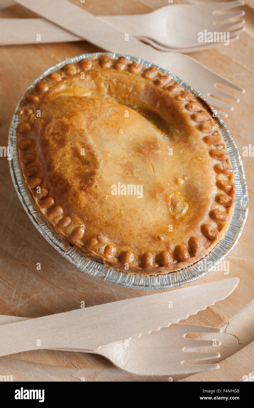 Savoury meat or steak pie in a foil tray with wooden cutlery - Stock Image
