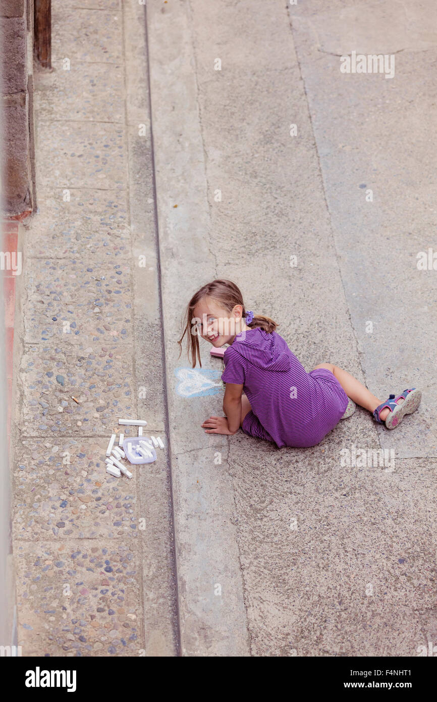 Smiling girl drawing with crayon on the street - Stock Image